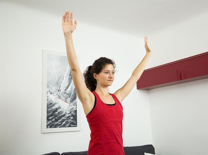 """Hebe deine Schultern mit der Übung """"Schultern drücken"""" hoch und löse Nackenverspannungen."""