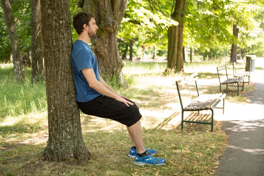 Sportlich Baumsitzen im Park.