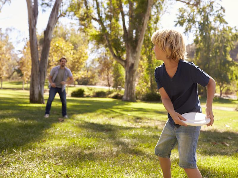 Sport mit Kindern: Frisbee spielen im Park.