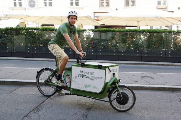 Dein vegetarisches Mittagessen wird umweltfreundlich mit dem Lastenrad zu dir geliefert.